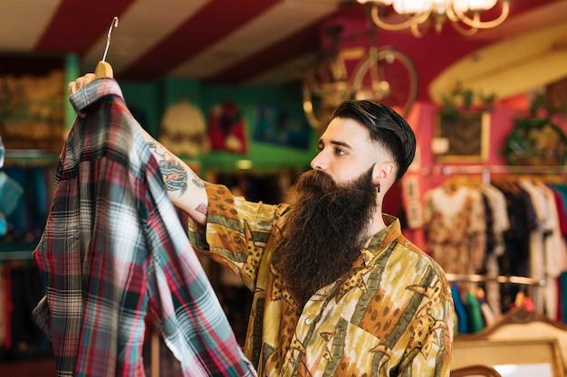 Модный молодой человек покупает одежду в магазине