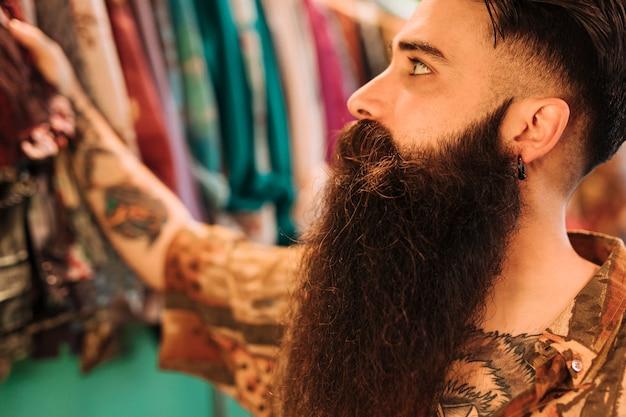 ハンサムなひげを生やした男の洋服店でのショッピング