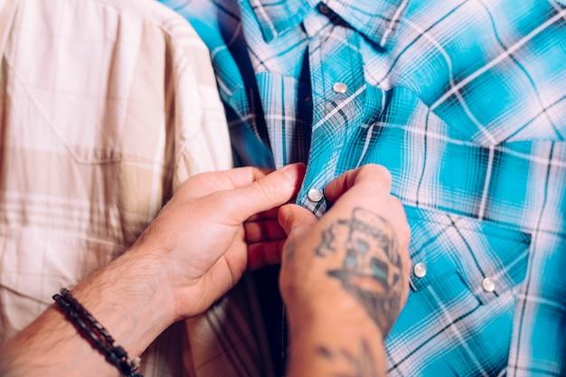 青いシャツのボタンを閉じる人間の手のクローズアップ