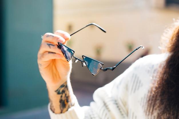 Крупным планом мужской руки, держащей солнцезащитные очки в руке летом