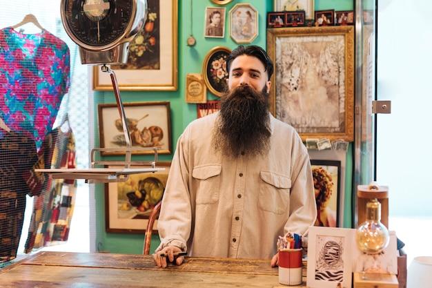 彼の店に立っているひげを生やした男性の所有者の肖像画