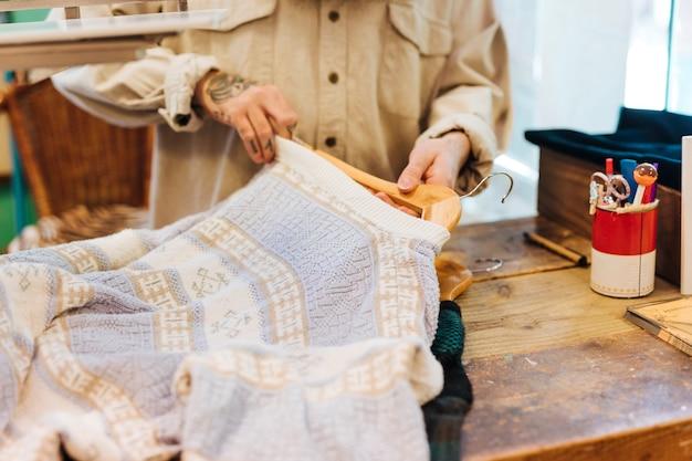 Крупный план мужской руки расставляет одежду на вешалке в магазине