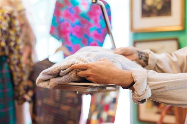 男性の売り手が衣料品店で体重計の布重量をチェック