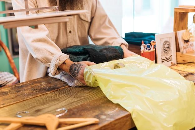 Хозяин мужика за прилавком упаковывает одежду в желтый полиэтиленовый пакет