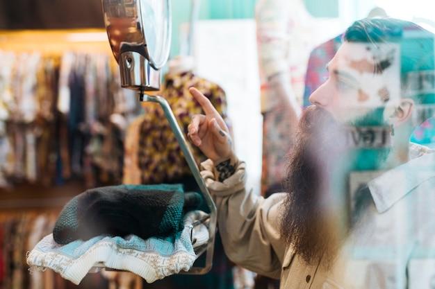 男性の売り手がガラスを通して見た衣料品店でスケールで生地の重さをチェック