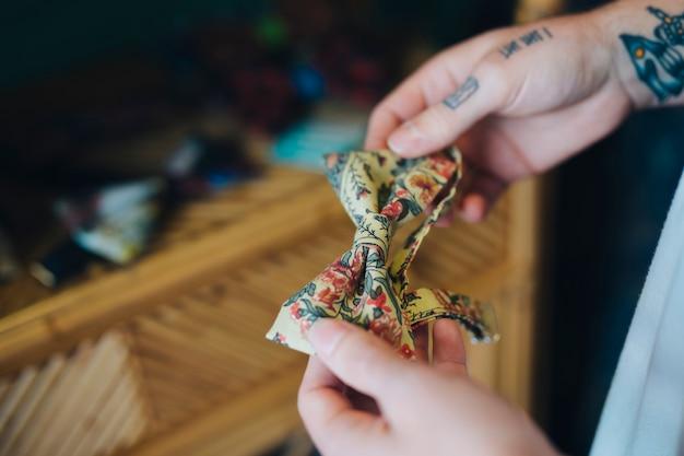 ビンテージ花蝶ネクタイを持っている人の手のクローズアップ