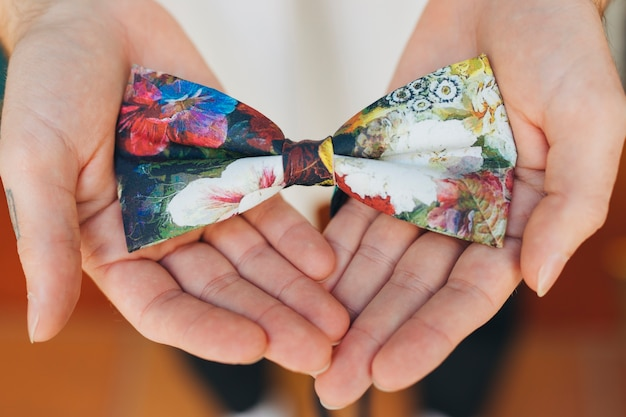 花の蝶ネクタイを示す男性の手