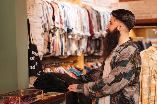 Бородатый молодой человек за прилавком, глядя на одежду, висит на железной дороге
