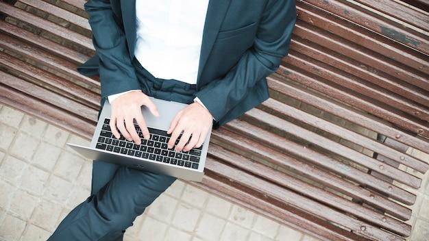 Повышенный вид бизнесмена, сидя на скамейке с помощью ноутбука