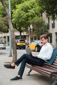 Молодой бизнесмен сидит на скамейке над тротуаром, используя ноутбук