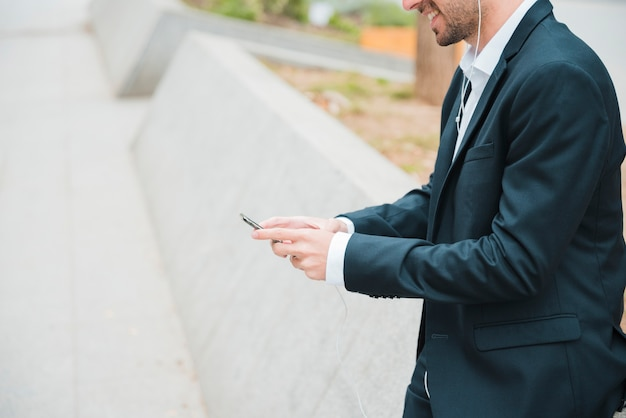 Улыбающийся портрет молодого бизнесмена с помощью смартфона