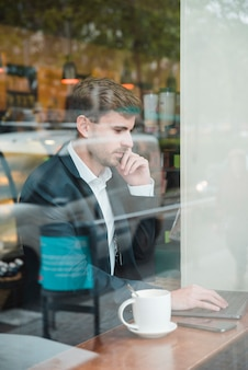 Крупный бизнесмен, используя ноутбук, принимая на мобильный телефон в кафе