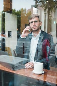 Стильный молодой бизнесмен разговаривает по мобильному телефону в кафе