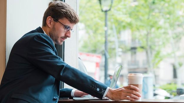 Крупный бизнесмен, используя ноутбук, держа одноразовые чашки кофе в кафе