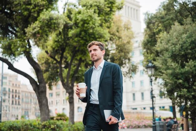 持ち帰り用のコーヒーカップとデジタルタブレットを保持している建物の前に立っている青年実業家の肖像画