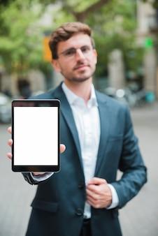 Портрет молодого бизнесмена показывая таблетку белого экрана цифровую