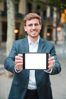 Успешный молодой бизнесмен показывая цифровую таблетку с белым экраном
