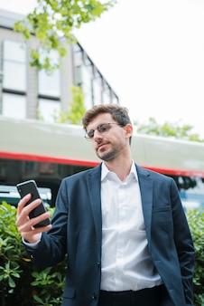 携帯電話を使用して建物の前に立っている青年実業家の肖像画