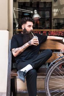 Портрет молодого человека, сидящего на скамейке и пьющего освежающее вкусное шоколадное молоко