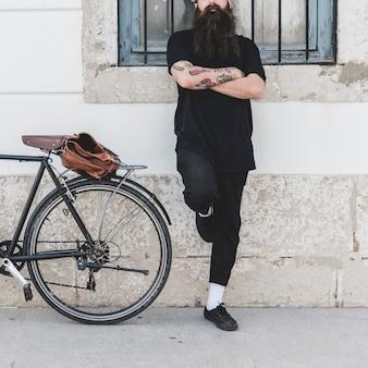 Бородатый молодой человек стоял у стены со скрещенными руками