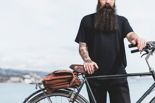彼の自転車で立っているひげを生やした若い男のクローズアップ