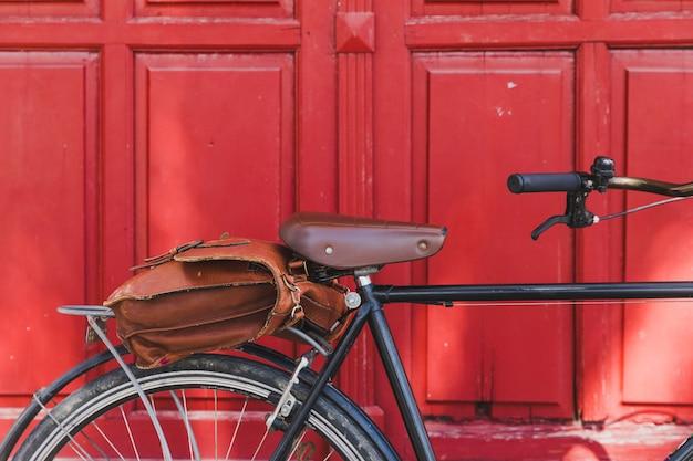 閉じた赤いドアに対して自転車に茶色のバッグ