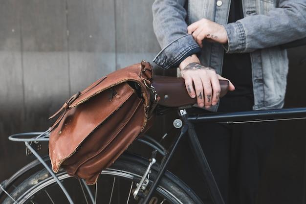 自転車に茶色のハンドバッグと立っている若い男