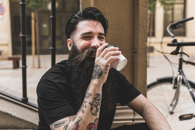 Бородатый молодой человек пьет кофе на вынос