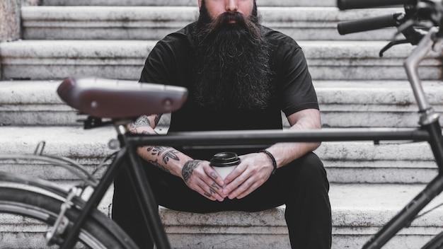 使い捨てのコーヒーカップを保持している階段の上に座っている若い男の前で自転車