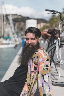 カメラを見て海岸に座って長いひげを持つ若い男の笑みを浮かべてください。