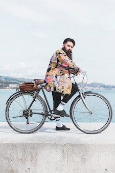 海岸近くの防波堤に彼の自転車を持つ若い男