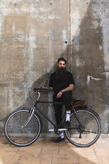 Портрет молодого человека с его велосипедом против выветрившейся бетонной стены