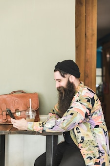 携帯電話を使用してカフェに座っている男の笑みを浮かべてください。