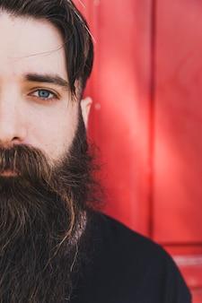 カメラを見てハンサムなひげを生やした若い男の半分の顔の肖像画