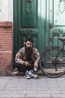 ヘッドフォンで音楽を聴くドアの隣に座っているハンサムな若い男