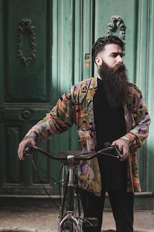 Бородатый велосипедист стоит перед древней зеленой деревянной дверью