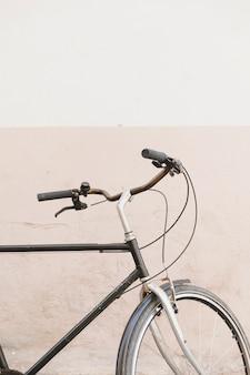 Крупный план ручки велосипеда перед двухцветной стеной