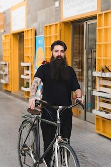 彼の自転車を持って通りを歩いている男