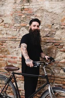 カメラを見て古いレンガの壁に立っている若い自転車