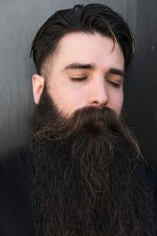 Крупным планом бородатый молодой человек с закрытым глазом