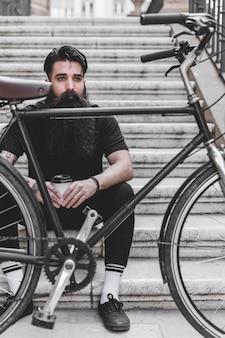 持ち帰り用のコーヒーカップを保持している階段の上に座っている若い男の前で自転車