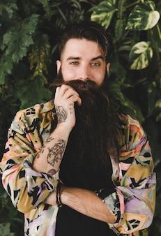 彼の口ひげを引いて彼の目を上げる若い男の肖像