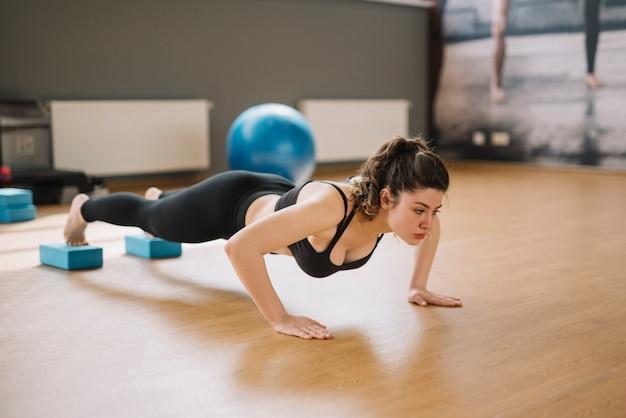 Тренировка молодой женщины в спортзале