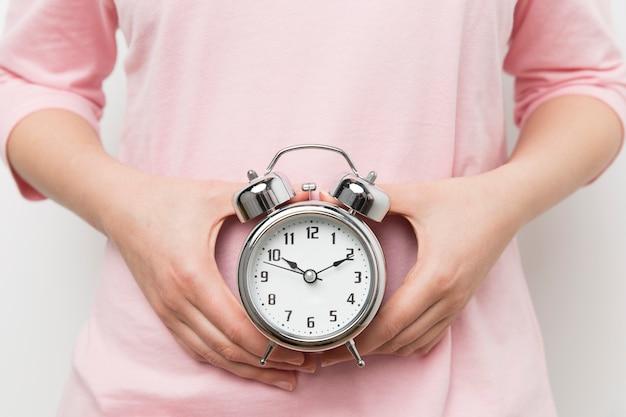 目覚まし時計を持って女の子
