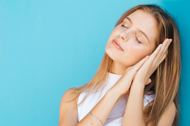 目を持つ若い女性は青い背景に対して眠っている閉鎖