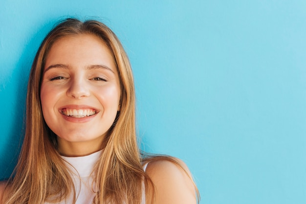 青い背景に対してカメラを見て陽気な若い女性の肖像画