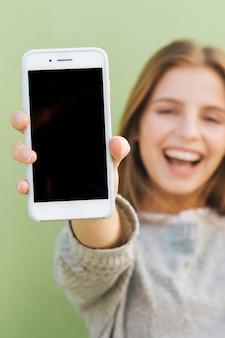 カメラに向かってスマートフォンを保持している美しい若い女性の幸せな肖像画