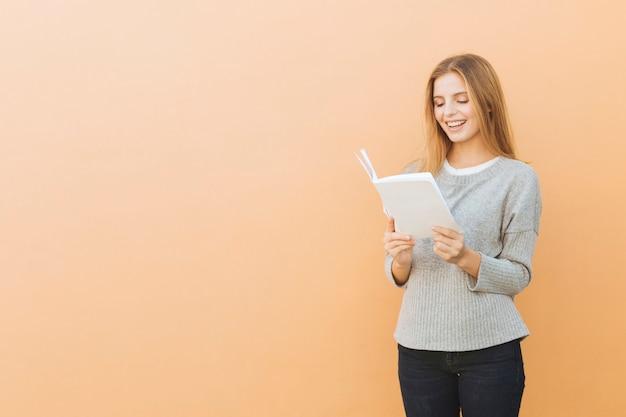 色付きの背景に対して本を読んで笑顔のかなり若い女性
