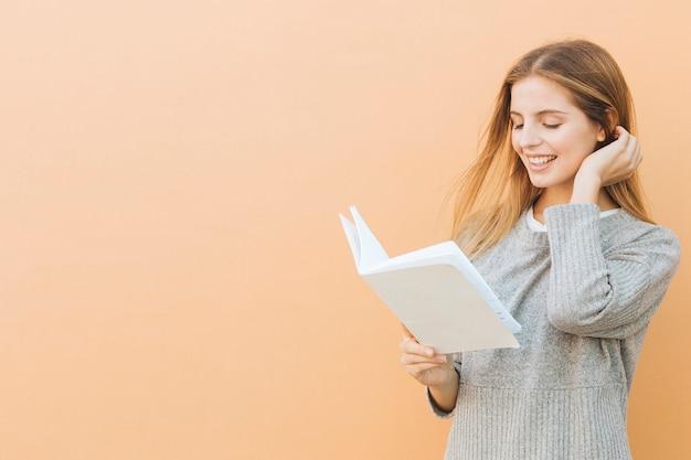 色付きの背景に対して本を読んで美しい若い女性のクローズアップ