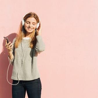 Удовлетворенная белокурая молодая женщина наслаждаясь музыкой на мобильном телефоне через наушники против розового фона